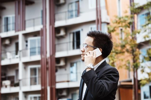 Concept business - homem de negócios conversando seriamente com seu projeto em seu celular
