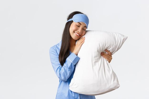 Concernente sonhadora linda menina asiática de pijama azul e máscara de dormir deitada na cama com os olhos fechados e abraçando o travesseiro, sorrindo despreocupada como tendo uma boa noite de sono, fundo branco de pé.