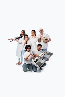 Concerto de uma família indiana de seis pessoas tocando instrumentos musicais em um grupo e uma senhora cantando, em pé contra um fundo branco