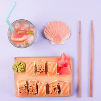 Concha de vieira; suco de toranja; pauzinhos; sushi de salmão servido com wasabi e gengibre em conserva em cortar placa contra o pano de fundo roxo