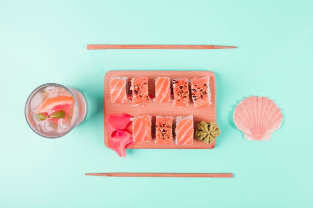 Concha de vieiras e suco de toranja com sushi de salmão servido com wasabi e gengibre em conserva na placa de desbastamento contra pano de fundo de hortelã