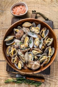 Conchas cozidas no vapor moluscos vongole em um prato de madeira