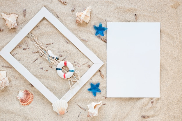 Conchas do mar com moldura e papel em branco na areia