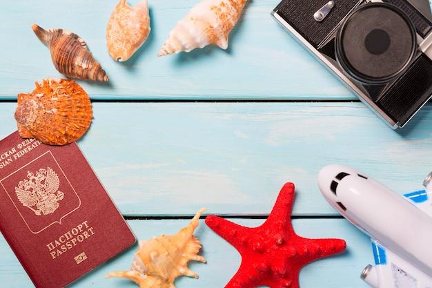 Conchas do mar com passaporte, avião de brinquedo e câmera retro ou mesa de madeira azul clara.