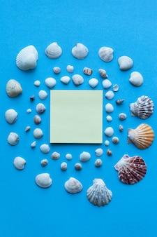 Conchas do mar e areia do mar sobre fundo azul.