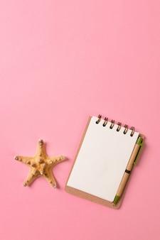 Conchas do mar e um caderno em um fundo rosa
