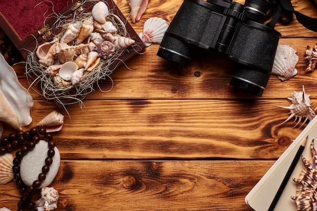 Conchas do mar na pequena caixa de madeira aberta ou caixão no fundo de madeira cercado por outras conchas do mar, pedras, com chapelim, binóculos velhos, lápis e caderno