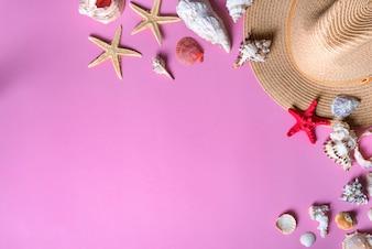 Conchas do mar no fundo violeta pastel com chapéu de palha - fundo das férias de verão.