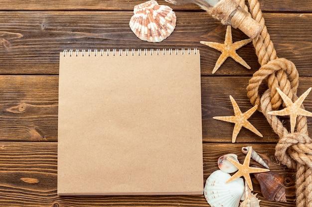 Conchas e bloco de notas na mesa de madeira intop vista com espaço de cópia