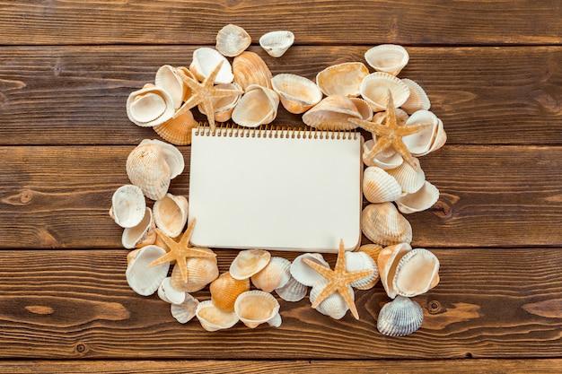 Conchas e bloco de notas na mesa de madeira na vista superior com espaço de cópia