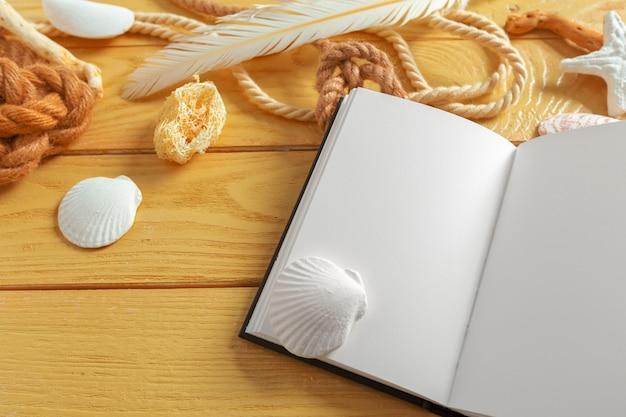 Conchas e bloco de notas na mesa de madeira. vista superior com espaço para texto