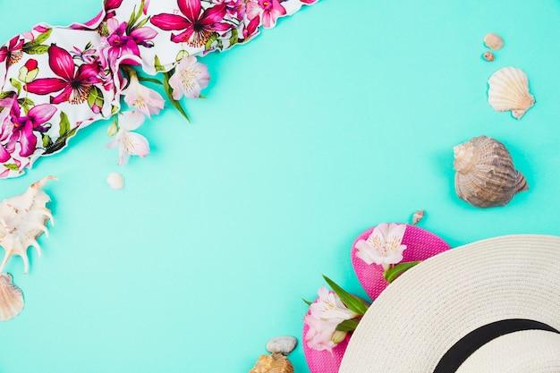 Conchas e maiô perto flip-flops com chapéu