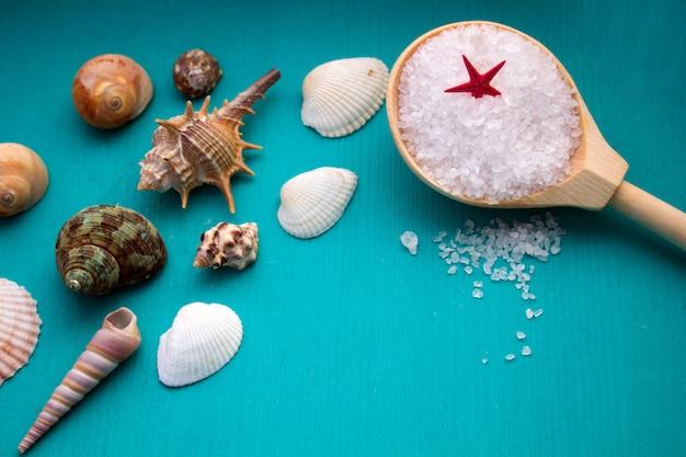 Conchas e sal do mar sobre fundo azul de madeira
