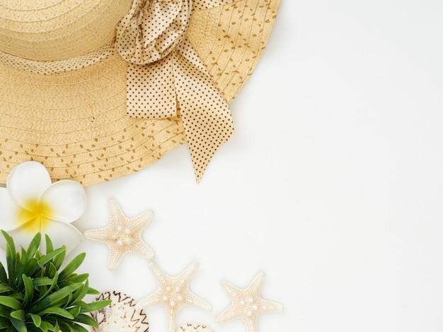 Conchas, estrelas do mar, chapéus de palha em um fundo branco
