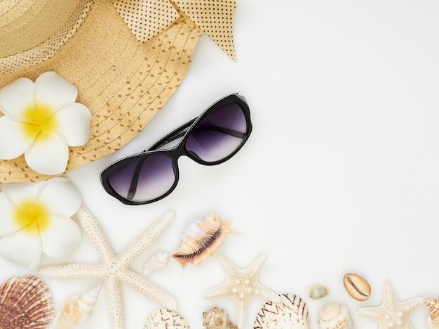 Conchas, estrelas do mar, chapéus de palha, óculos escuros em um fundo branco