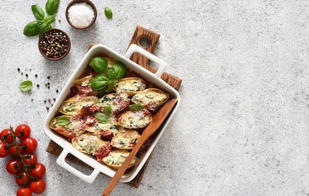 Conciglioni italiano cheio. conciglioni com ricota assada em molho de tomate com parmesão em uma superfície de concreto. macarrão assado com ricota.