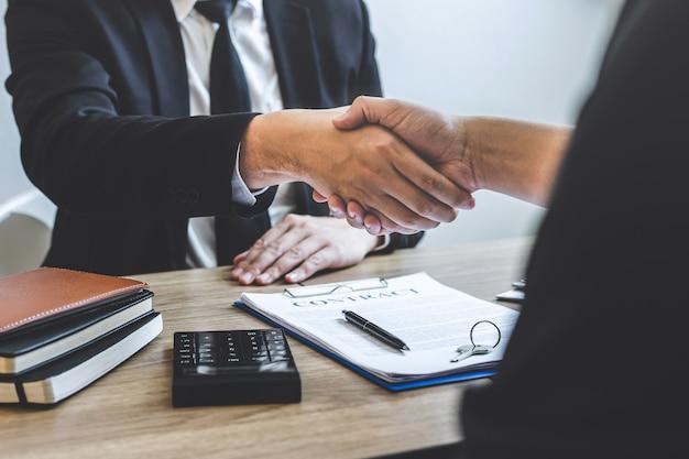 Concluindo o sucesso do negócio imobiliário, o corretor e o cliente cumprimentam-se após assinar o formulário de solicitação de contrato aprovado, referente à oferta de empréstimo hipotecário e seguro residencial