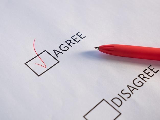 Concordo e discordo nas caixas de seleção na marca da folha branca concorda com caneta vermelha.
