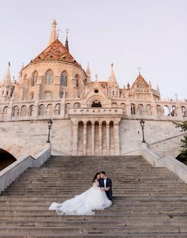 Concurso casal de noivos está sentado na escada de um antigo edifício histórico de pedra na noite quente