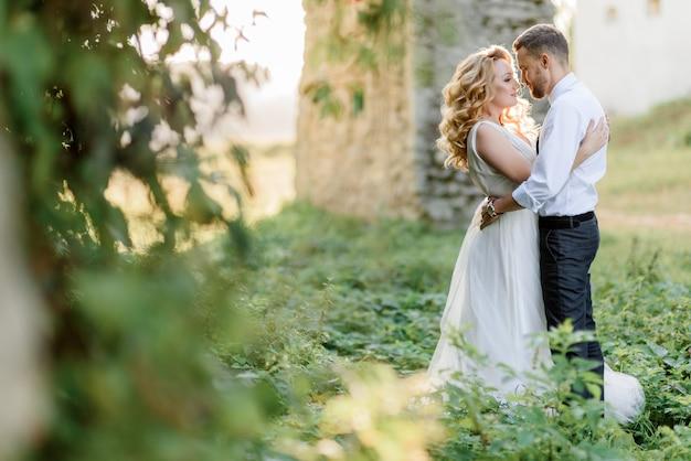Concurso casal está quase se beijando ao ar livre no dia quente e ensolarado, perto do edifício de pedra rodeado de grama verde