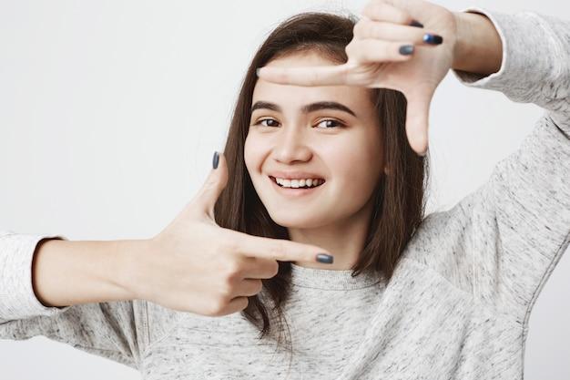 Concurso e sincera mulher caucasiana, com sorriso alegre e olhar caloroso, fazendo gesto de quadro com as mãos