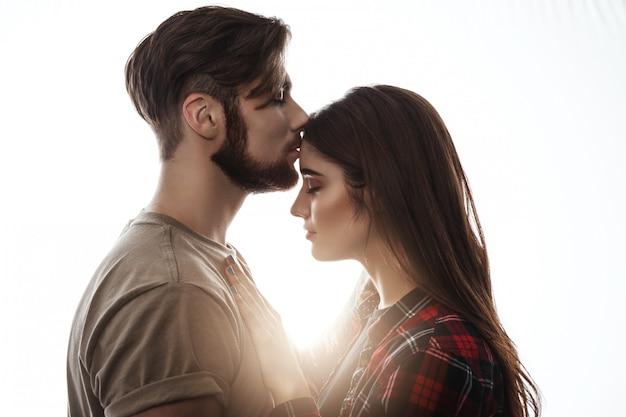 Concurso foto do jovem casal. homem beijando mulher na testa.
