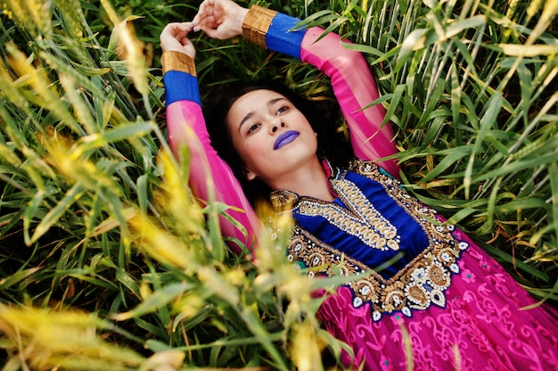 Concurso garota indiana em saree, com lábios violetas compõem colocadas em campo no pôr do sol. modelo elegante da índia.