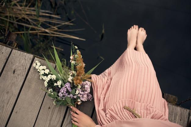 Concurso garota linda em um vestido cor de pêssego andando em uma ponte de madeira rural com um buquê de flores