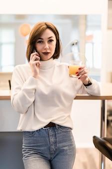 Concurso jovem de camiseta branca e calça jeans azul na cozinha falando ao telefone