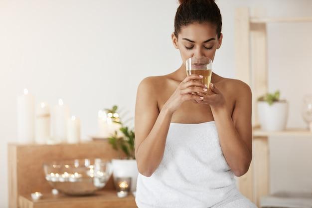 Concurso mulher africana, bebendo chá verde, descansando no salão spa.