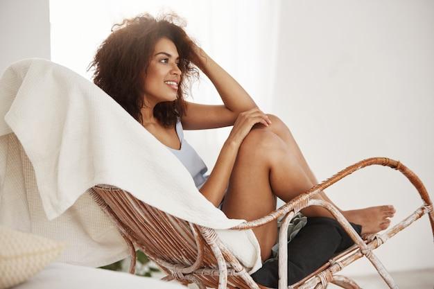 Concurso mulher africana bonita em roupa de noite sorrindo sentado na cadeira descansando relaxando em casa.