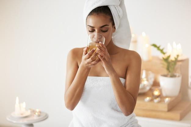 Concurso mulher africana com toalha na cabeça bebendo chá descansando no salão spa.