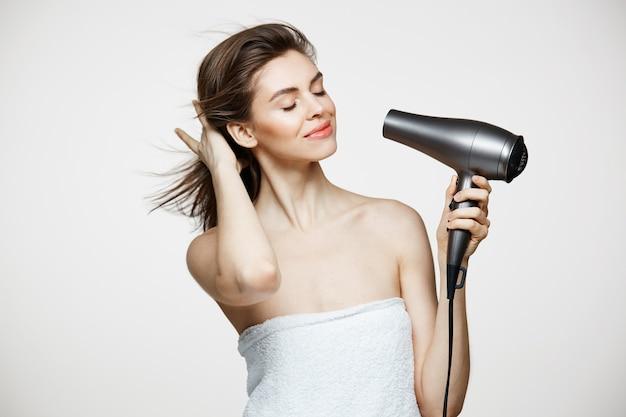 Concurso mulher bonita morena no cabelo de secagem de toalha sorrindo sobre bakground branco. olhos fechados. spa de beleza e cosmetologia.