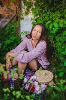 Concurso mulher descansando em bosques gramados com um lindo buquê de peônias e flores silvestres