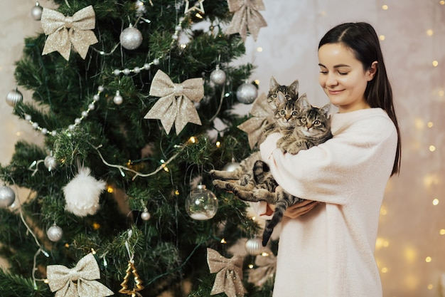 Concurso mulher feliz segurando e olhando seu gatinho três doce perto da árvore de natal.
