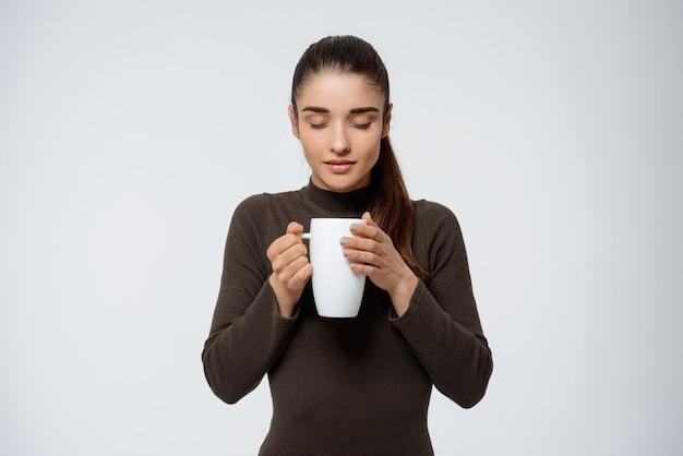 Concurso mulher sorridente, cheirando café delicioso