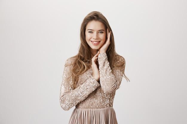 Concurso mulher sorridente, tocando a pele, usar vestido