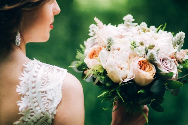 Concurso noiva segurando um buquê de casamento. noiva na natureza com um buquê de peônias.