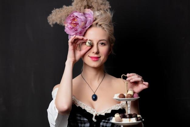 Condessa loira bonita com bombons de chocolate