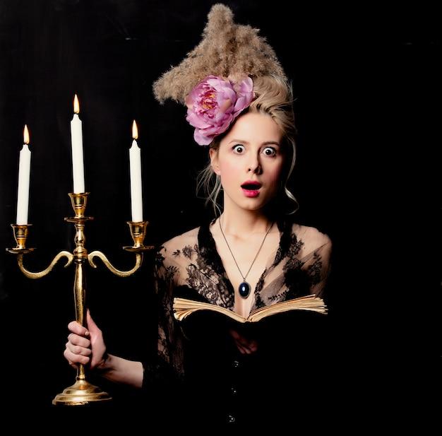 Condessa loira bonita com um livro e castiçal
