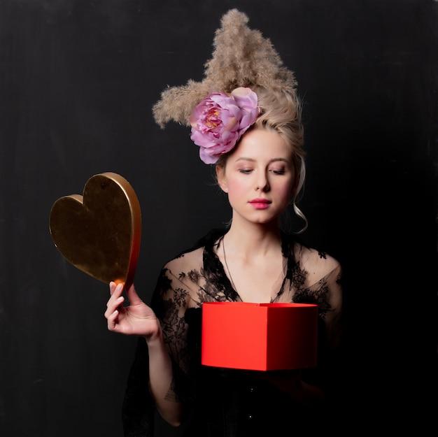 Condessa loira bonita com uma caixa de forma de coração