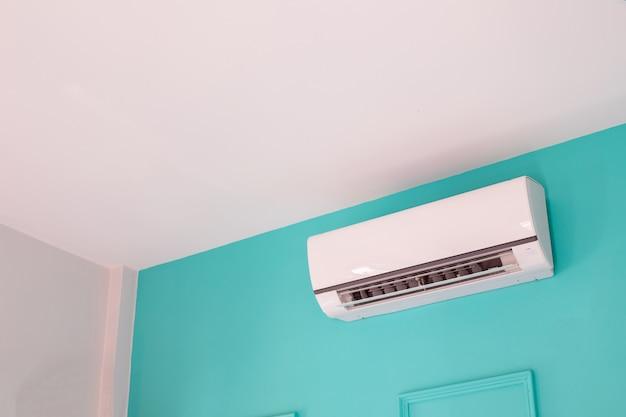 Condicionador de ar moderno na parede azul no quarto em casa, ninguém.