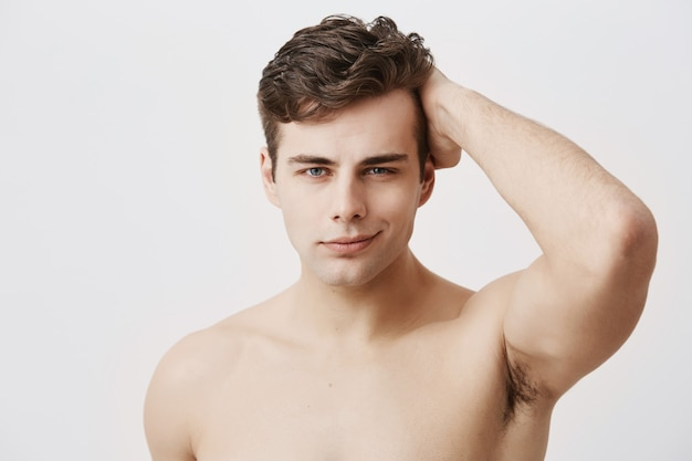 Condifente jovem europeu com corte de cabelo à moda e olhos atraentes, estar nu, tocando o cabelo escuro, posando. belo modelo masculino com pele limpa saudável sorrindo suavemente