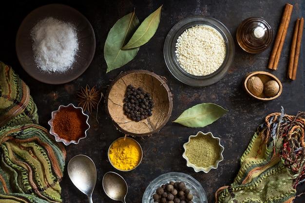 Condimentos alimentares secos e sal em uma superfície escura