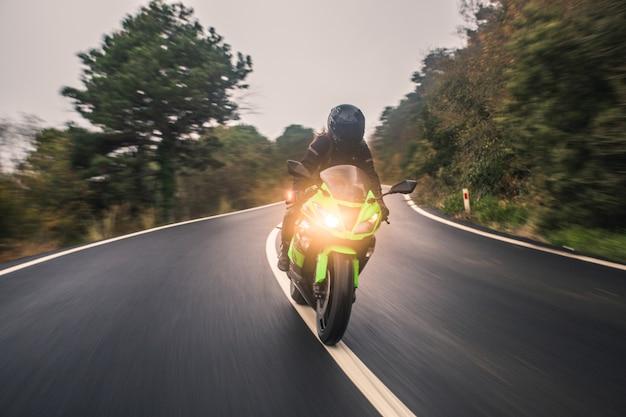 Conduzindo a motocicleta de cor verde neon na estrada, vista frontal.