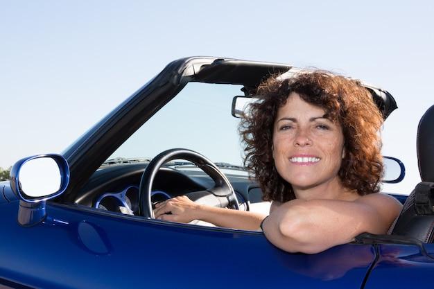 Conduzindo a mulher no carro azul do esporte no verão