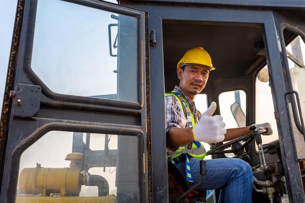Conduzindo o trator de rodas pesadas de trabalhador, escavadeira de escavadeira com retroescavadeira descarregando areia trabalha no canteiro de obras.