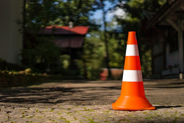 Cone alaranjado vermelho com uma listra branca na estrada da pedra de pavimentação. conduza o conceito de segurança e construções. fechar-se.