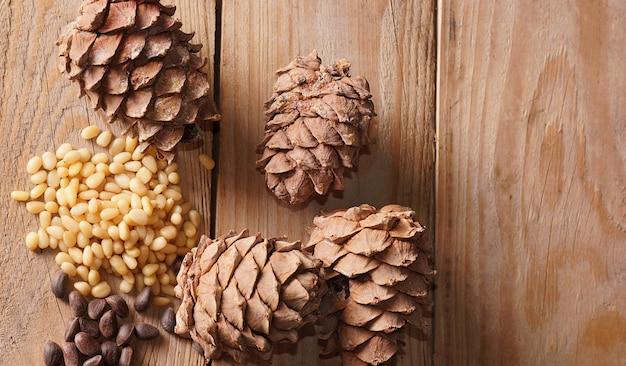 Cone de cedro e pinhões repousam sobre uma mesa de madeira