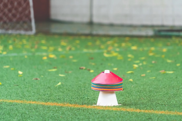 Cone de esporte colorido e marcador para futebol e outro treinamento esportivo em um campo de grama do prado